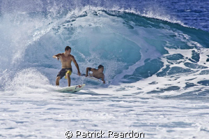 A crowded wave at Pipeline, North Shore, Oahu. by Patrick Reardon