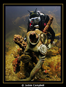 Diver with gas masks in one of the cargo holds of the Fuj... by Jackie Campbell