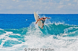 A surfer is frozen in time and space as he carves out the... by Patrick Reardon
