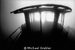 The sun bursts through the skeletal remains of the wheelh... by Michael Grebler