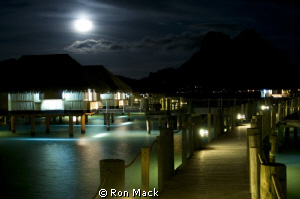 Resort huts over water with main island of Bora Bora in b... by Ron Mack