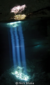 Light beams in Taj Maha Cenote, Riviera maya, Mexico. by Nick Blake