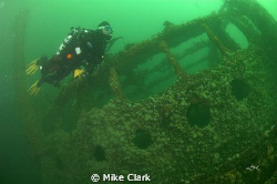 Diver fins past the bridge of the Hispania Wreck by Mike Clark
