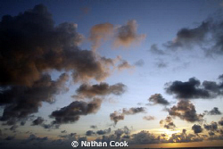 Sunset clouds over the water in Cozumel Mexico. by Nathan Cook