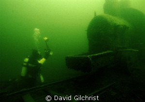 Diver prepares to take photograph of one of two locomotiv... by David Gilchrist