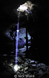 A single beam of light in the darkness of Dos Ojos cenote... by Nick Blake