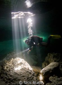 """Into the Light"". Diver in sunbeams in Taj Maha Cenote, ... by Nick Blake"