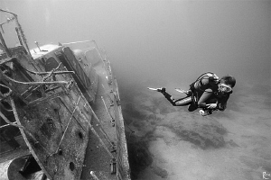 Female diver explores a shipwreck. B/W shot, ambient ligh... by Rico Besserdich