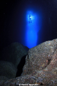 Diver in the entrance of a cave by Patrick Neumann