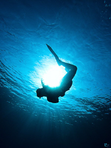 """A female freediver bends around the sun""