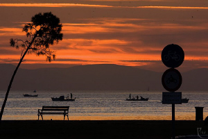 Sunset at the bay of Izmir with some fishermen heading ho... by Rico Besserdich