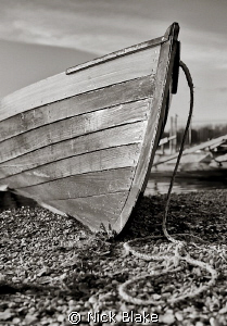 A small boat rests on the shore of Derwent Water in  the... by Nick Blake