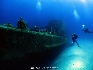 Divers approaching the wreck of the P31 off Comino Island by Ros Parmenter