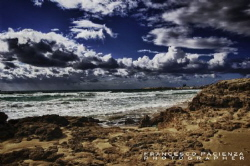 Sands, rocks, sea and sky with clouds. by Francesco Pacienza