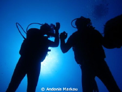 Silhouette of two divers by the wreck HMS cricket.  by Andonis Markou