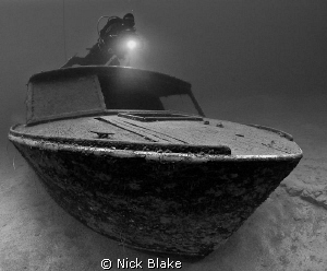 Boat wreck and diver Wraysbury lake, Middlesex, UK.  by Nick Blake