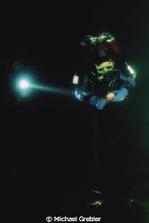 Divers working together in the intense darkness of a floo... by Michael Grebler