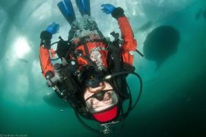upside down diver walking under ice by Mathieu Foulquié