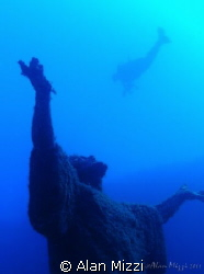 Diver swimming over statue of Jesus. by Alan Mizzi