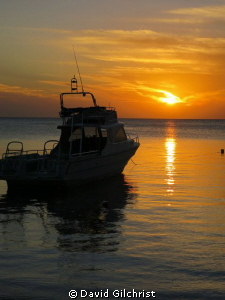 Sunset,West End, Roatan Honduras with  Native Sons Dive b... by David Gilchrist
