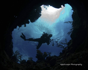 Andrew with camera looking back down this coral chimney. by Richard Apple