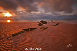 Sunset over a shipwreck by Mike Clark