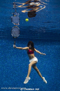 Woman playing tennis underwater, just for fun!! by Christian Vizl