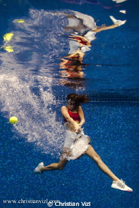 Woman playing tennis underwater, just for the fun of it! by Christian Vizl