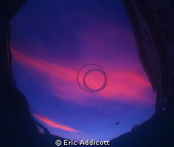 Sunset with bubble rings from the bottom of my pool. by Eric Addicott