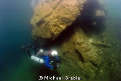 Side-mount diver examines one of the supporting rock pill... by Michael Grebler