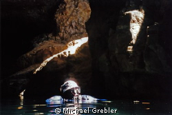 Cave diver surfacing in the cavern section of a flooded m... by Michael Grebler