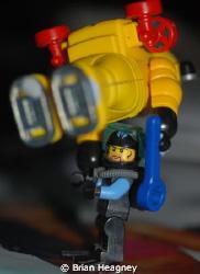 Lego diver prepares Playmobil diver for deep descent. by Brian Heagney