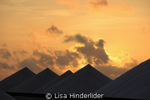 Morning sun rising behind the salt piles- Bonaire by Lisa Hinderlider