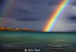 This is a Rainbow over Torch Lake, in Michigan. The fall ... by John Peal