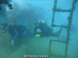 My bigger son, diving among a sunken ship by Hector Velez