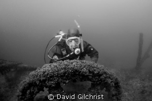 Diver poses at the fly wheel of pump in Sherkston Quarry. by David Gilchrist