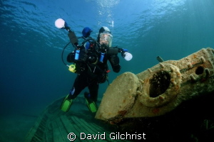 Diver/photographer poses at the engine of the steam tug '... by David Gilchrist