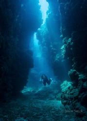 Diver navigating a passage between the reefs by Jason Sintek