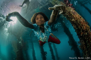 Papuan Girl Posing under Aborek Jetty by Henrik Gram Rasmussen