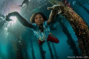 Papuan Girl Posing under Aborek Jetty by Henrik Gram Rasmussen