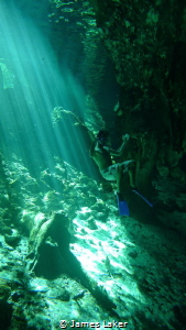 Ambient light photo of snorkeller in Grand Cenote near th... by James Laker