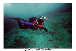 Side-mount diver with helmet cam and lights descending in... by Michael Grebler