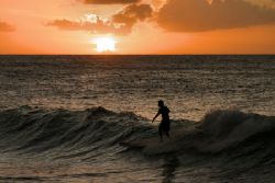 Surfing at sunset @ Turtle Bay Oahu by Glenn Poulain