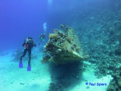 Photographer and wreck of a yacht, Red Sea by Paul Spiers