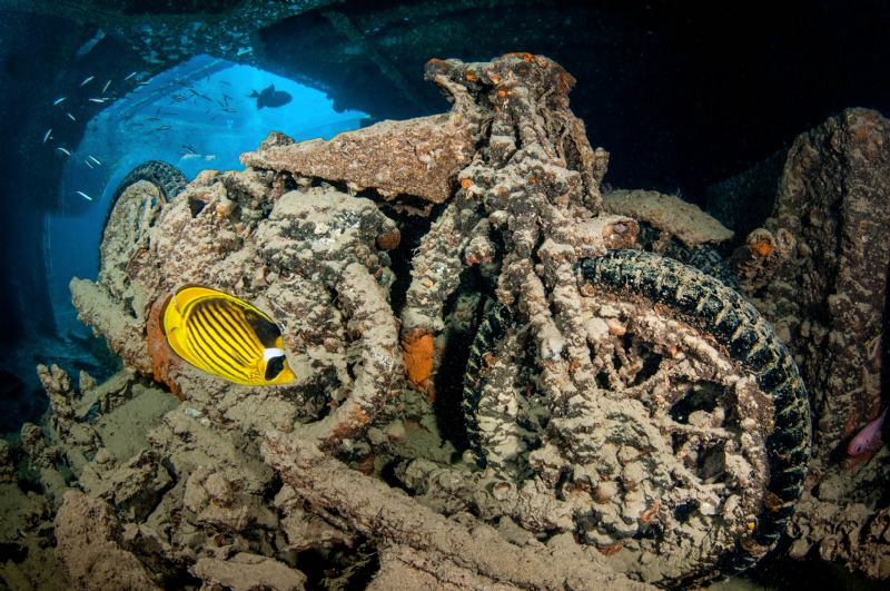 A motorbike on the wreck of SS Thistlegorm.  Slow shutter to capture the blue light coming through the hold hatchway.