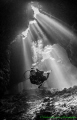 Cathedral lighting illuminates diver inside a cave at St John Reef, Egyptian Red Sea