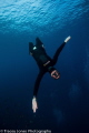 Free diver falling towards the camera with open arms