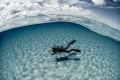 Overunder shot. Diver on a white sandy ocean floor.