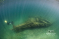 Under streaming light rays, a photographer shoots images of the stern of the Joseph S. Fay shipwreck in Lake Huron. The ship sunk in a storm when the schooner it was towing twisted, ripping off the stern of the Fay.