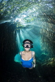 Freediver Natalia swimming through the sunlight broken up by the freshwater mangroves of Cenote Cristalino